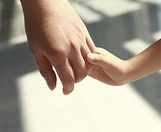 parent holding child's hand after discussing family law issues including divorce and child support with divorce attorneys at nalder law office in idaho falls