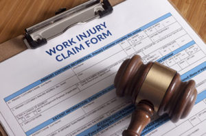 work injury claim form with a legal gavel on top of it being represented after an injury at work and needing a workers compensation attorney in idaho falls